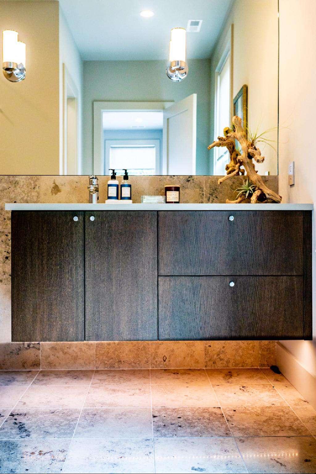 Spa-inspired en-suite bathroom design with tropical rain showerhead and luxury bath amenities.