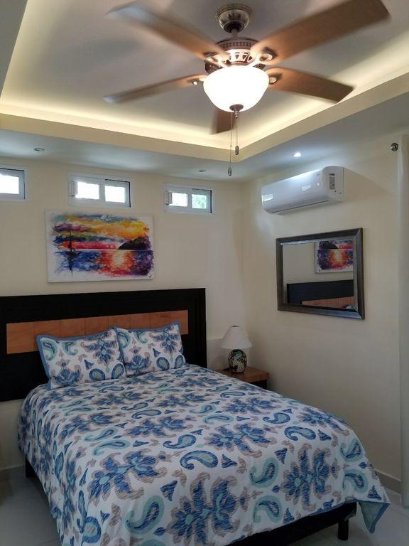 Bedroom with Queen Bed, air conditioner, ceiling fan and nightstands.