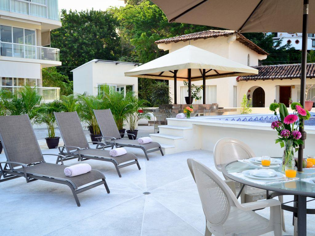 Loungers, bar and grill area, pool and seating on pool deck.