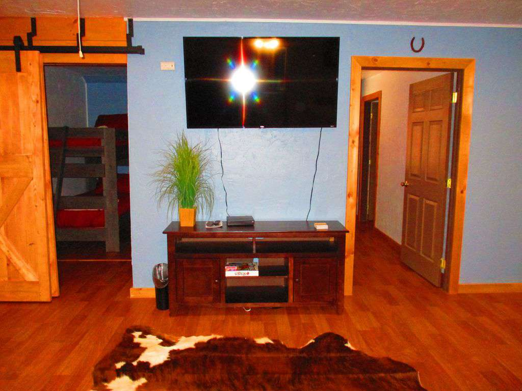 Living room upstairs with Large smart tv small room to the left twin bunk beds