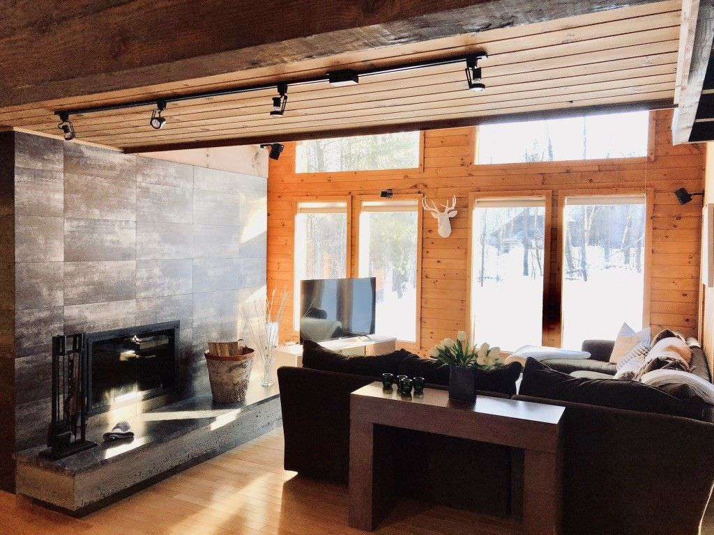 Step into sunlight, wood beams, and an inviting family room with dramatic fireplace.