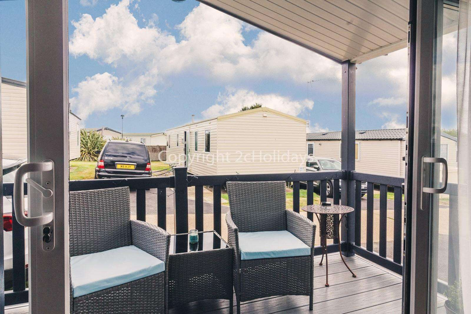 Beautiful outside, sheltered, enclosed decking with rattan furniture!