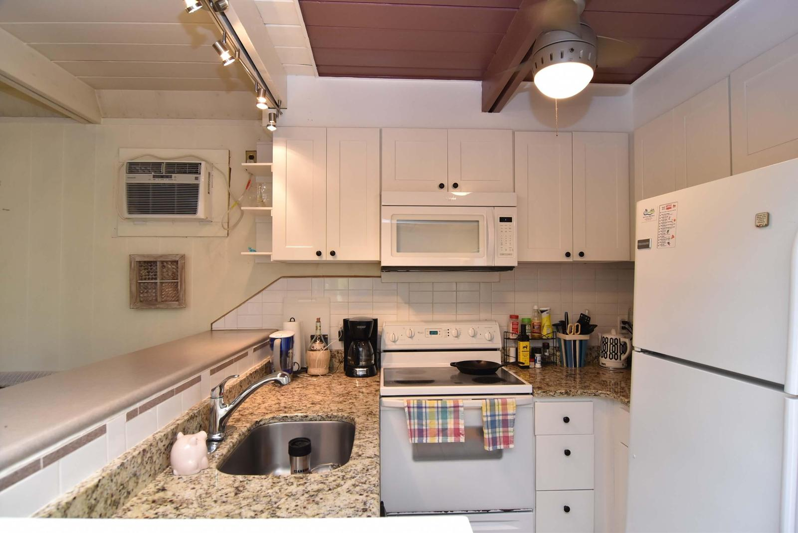 Full kitchen with granite countertops open to dining and sitting rooms