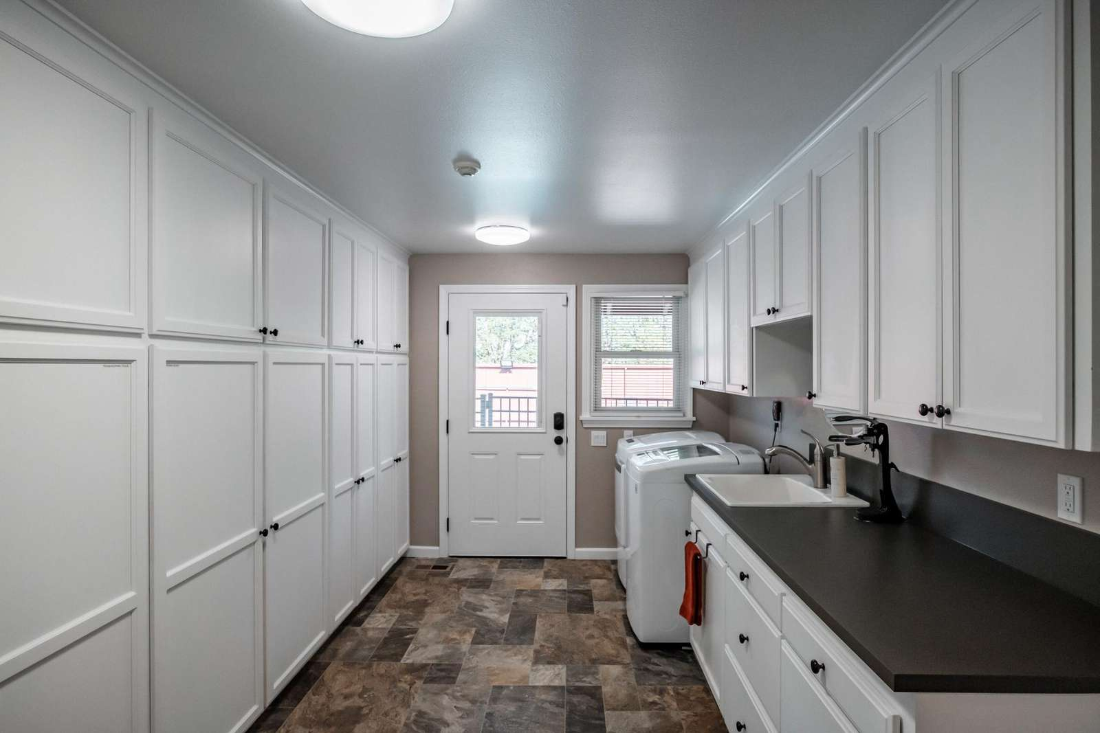 Utility Room with washer, dryer, utility sink and storage.