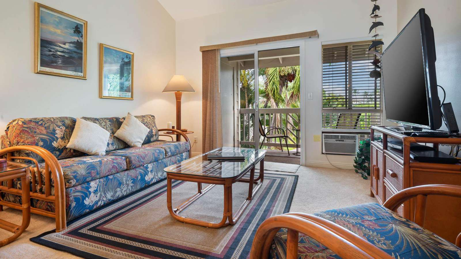Roomy living area with large TV and lanai access.