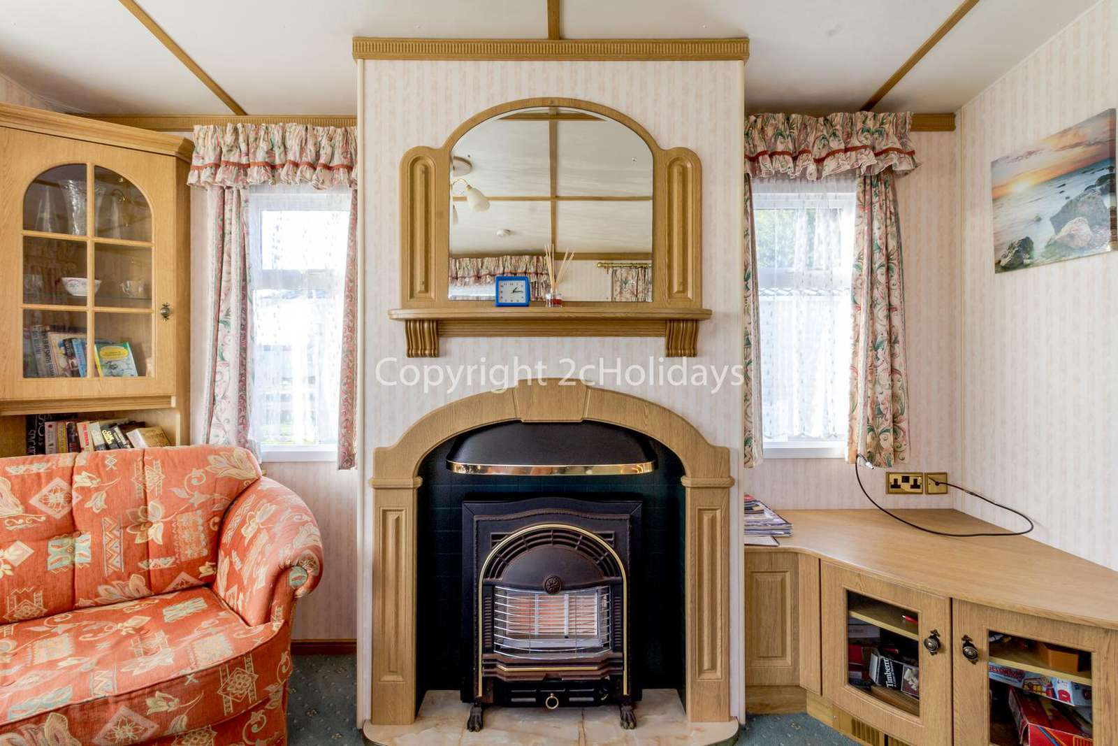 A homely lounge with a double sofa bed and a gas fire