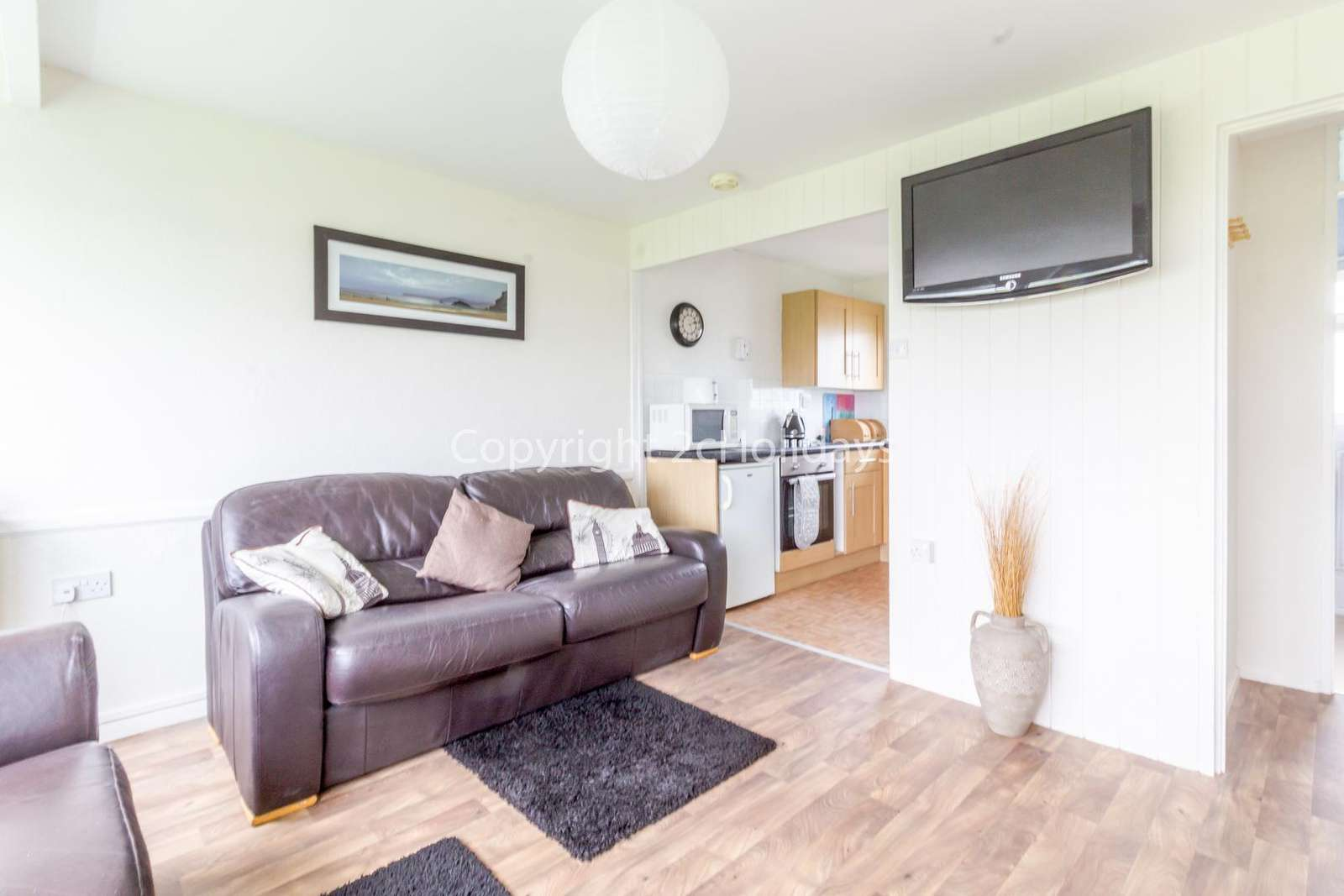 Spacious living area with a TV leading to the kitchen