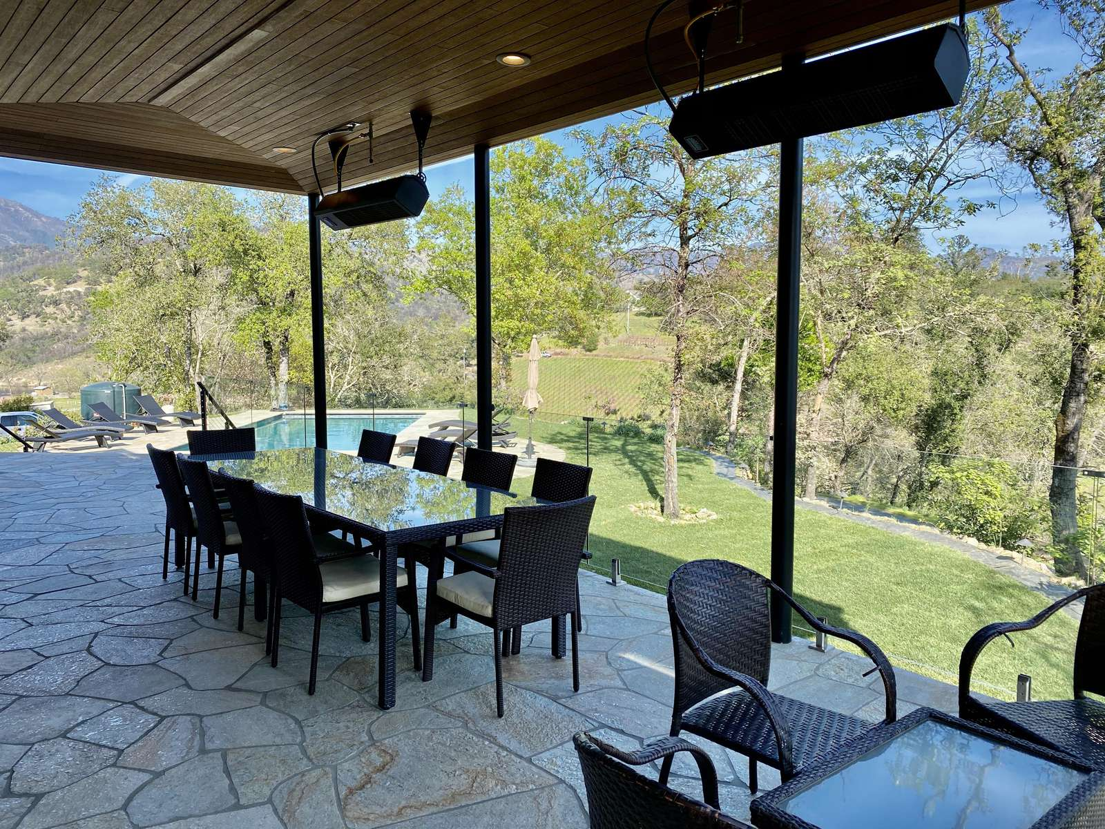 Outdoor patio and dining area overlooking pool and grassy areas