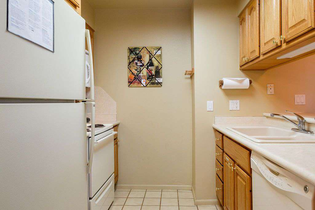 Kitchen straight view including fridge and sink