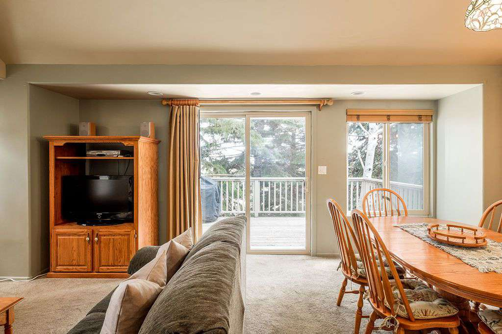 Living room with TV and view of private deck