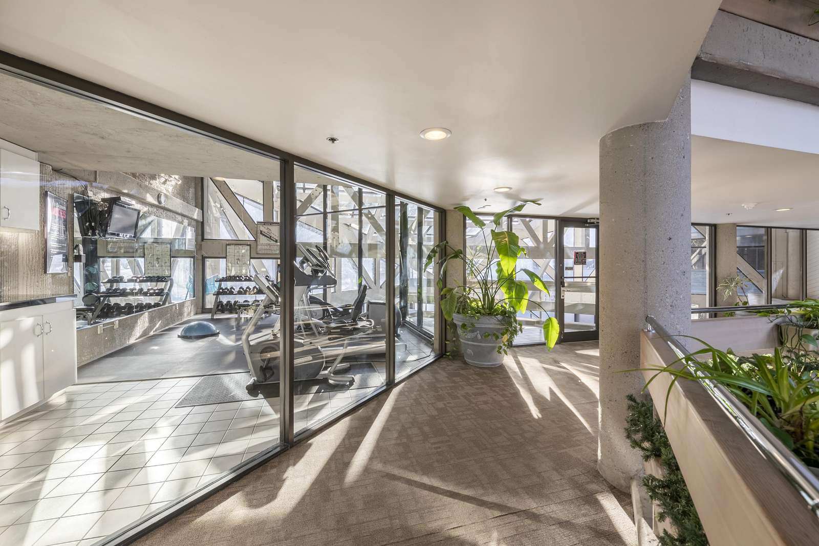 Large gym located on the condo level overlooks the pool