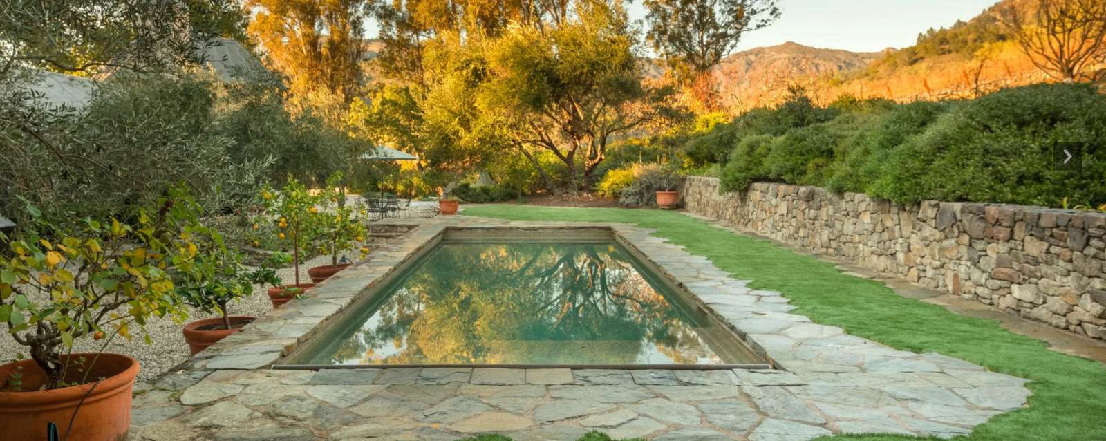 Heated pool w/ cover to left of and behind Villa 1