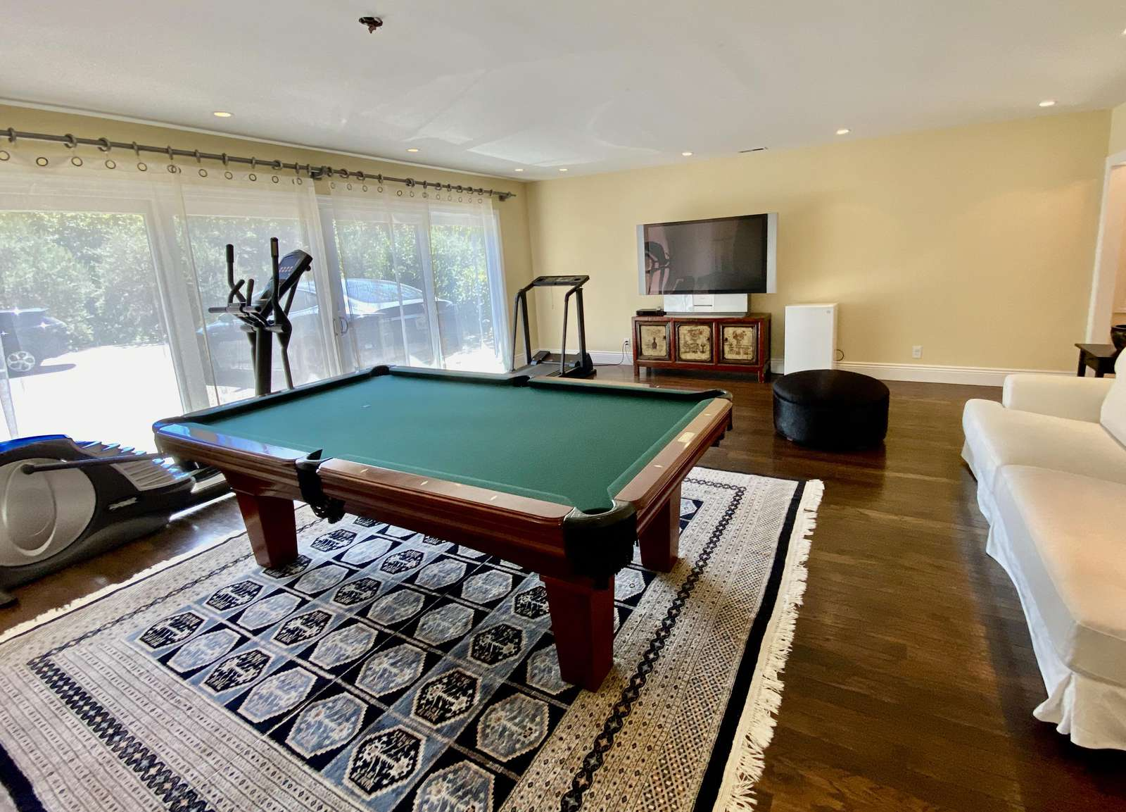 Lower level game room w/ pool table, large TV and exercise equipment