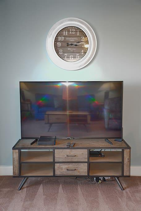 """Living Room with a 65"""" Samsung Smart TV with comcast cable and a dvd player along with a sofa sleeper with a queen size pullout."""