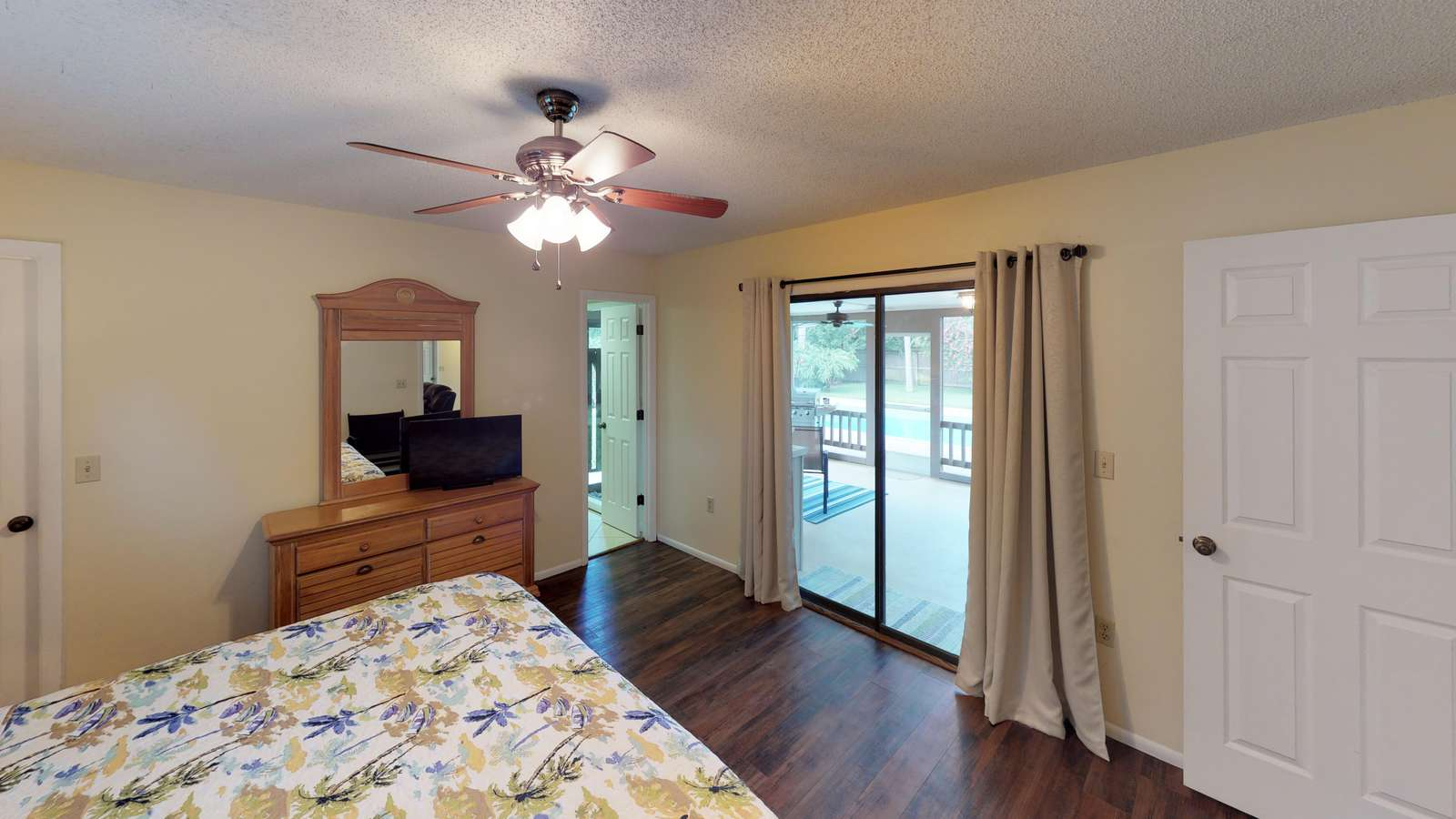 Primary Bedroom with king bed, private bathroom and view to lanai/pool