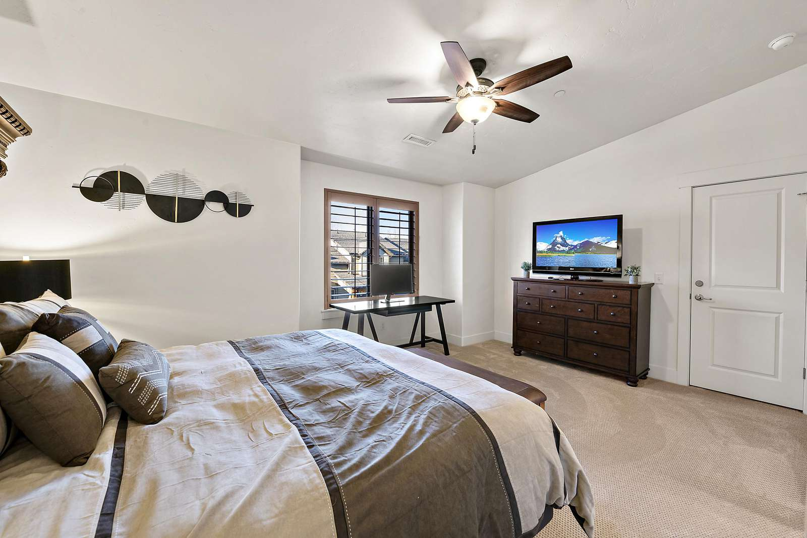 Master bedroom with window views and dresser