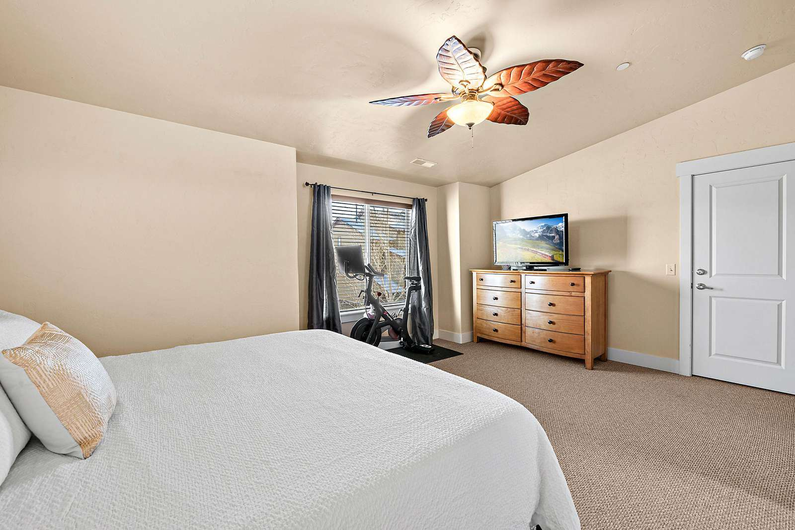 Master bedroom features exercise bike and TV