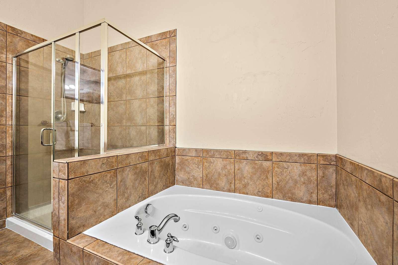 En-suite bathroom with standing shower and bathtub