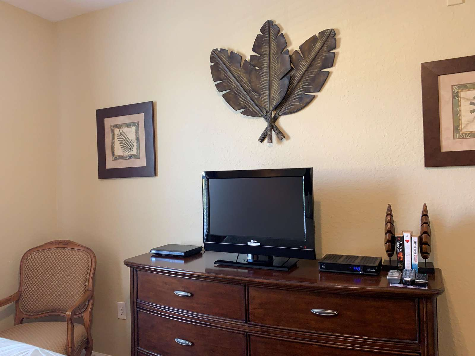 Flat screen TV, DVD, and chair in second bedroom